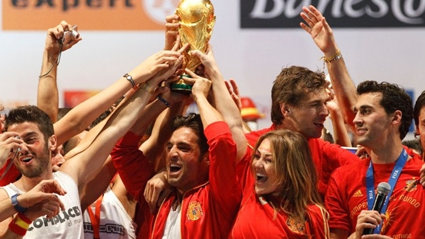 Spanish musicians David Bisbal and amaia Montero hold on the trophy on a stage set up for the Spanish team victory ceremony on July 12, 2010 in Madrid, Spain.
