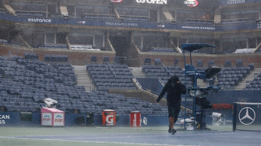 Sept. 8, 2012: A television crewman struggles during a rain delay at the 2012 US Open tennis tournament in New York.