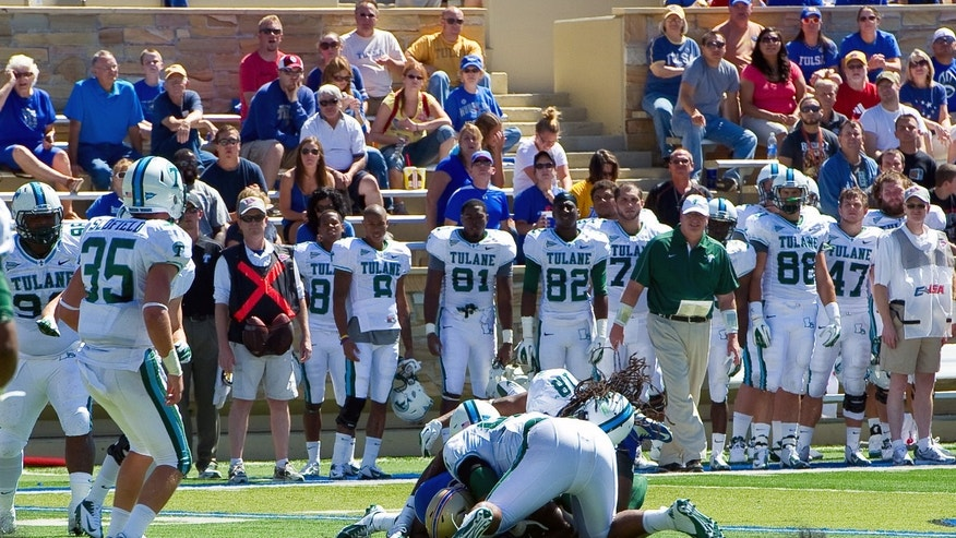 Sept. 8, 2012: In this photo provided by the University of Tulsa, Tulane's Devon Walker (18) and Julius Warmsley (92), center foreground,  tackle Tulsa's Kenny Welcome during the first half of an NCAA college football game in Tulsa, Okla.