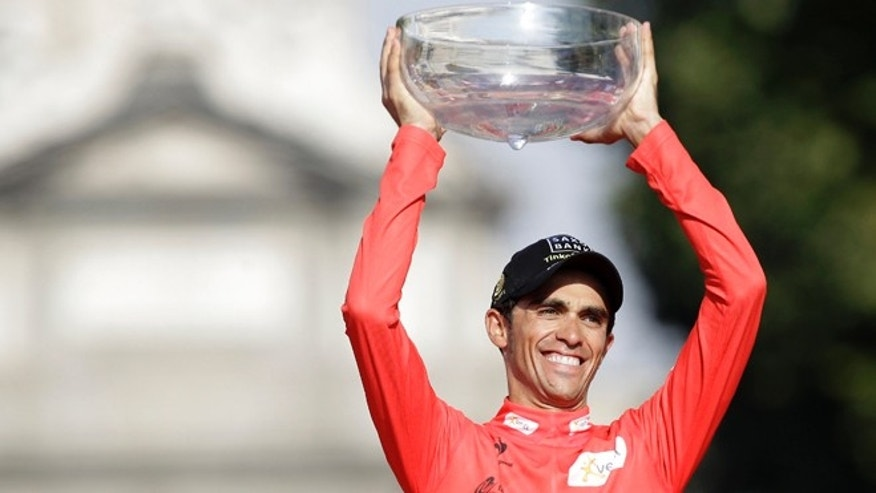 Saxo Bank Team cyclist Alberto Contador celebrates at the podium as he holds Spanish vuelta cycling race trophy after riding the final stage along 115 km (71 miles) from Cerdedilla to Madrid, on Sunday, Sept. 9, 2012. (AP Photo/Alberto Di Lolli)