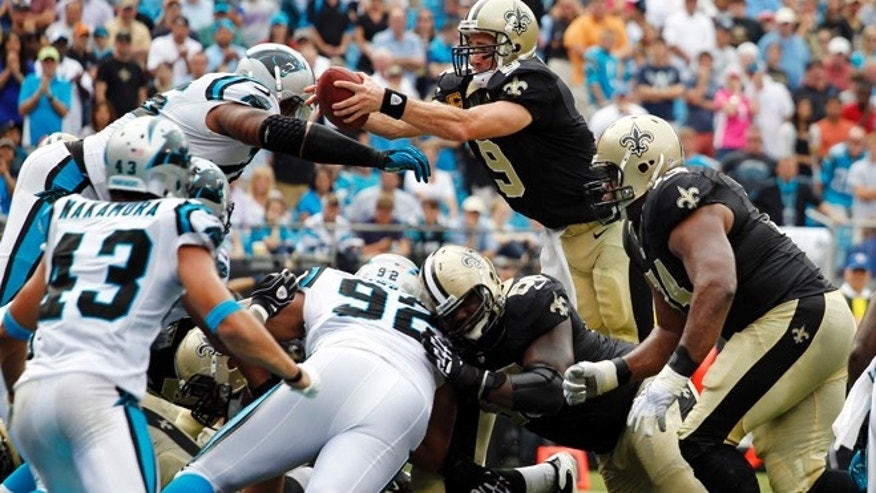 Sept. 16, 2012: New Orleans Saints' Drew Brees (9) reaches the ball over the goal line for a touchdown against the Carolina Panthers during the fourth quarter of an NFL football game in Charlotte, N.C. The Panthers won 35-27.