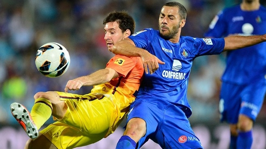 GETAFE, SPAIN - SEPTEMBER 15: Leo Messi of FC Barcelona duels for the ball with Mehdi Lacen of Getafe CF during the La Liga match between Getafe CF and FC Barcelona at Coliseum Alfonso Perez on September 15, 2012 in Getafe, Spain.