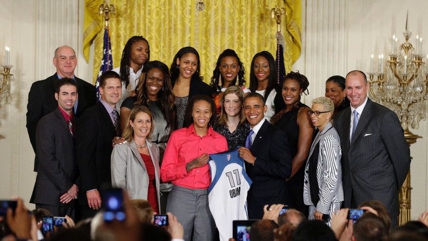 Sept. 18, 2012: President Barack Obama, center right, holds up a Lynx team basketball jersey presented to him by Seimone Augustus, center left, as he honors the WNBA Champion Minnesota Lynx, in a ceremony in the East Room of the White House in Washington.