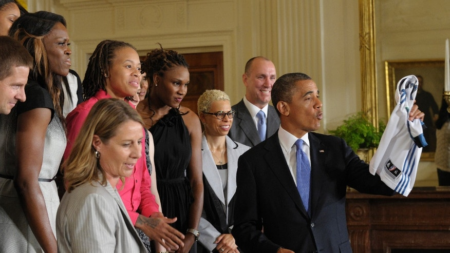 Sept. 18, 2012: President Barack Obama holds up a Lynx team basketball jersey that was presented to him in a ceremony honoring the WNBA Champion Minnesota Lynx, in a ceremony in the East Room of the White House in Washington.