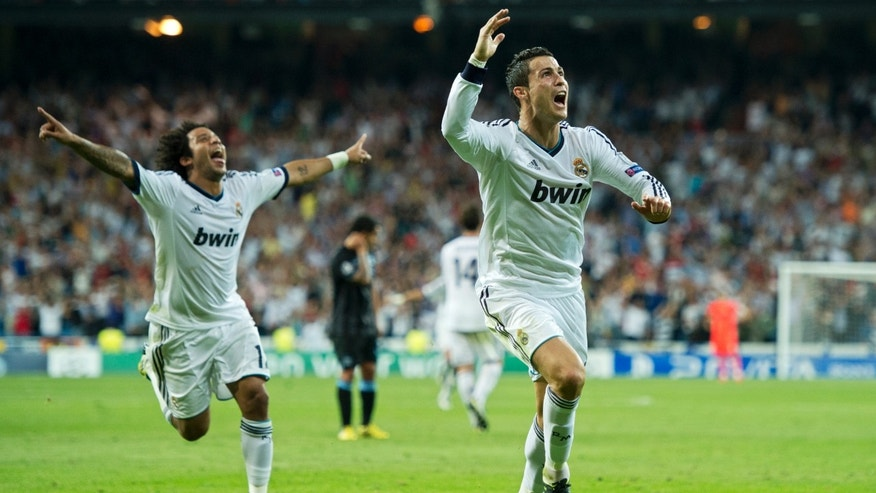 MADRID, SPAIN - SEPTEMBER 18:  Cristiano Ronaldo (R) of Real Madrid celebrates scoring his sides winning goal during the UEFA Champions League group D match between Real Madrid and Manchester City FC at the Estadio Santiago Bernabeu on September 18, 2012 in Madrid, Spain.  (Photo by Jasper Juinen/Getty Images)