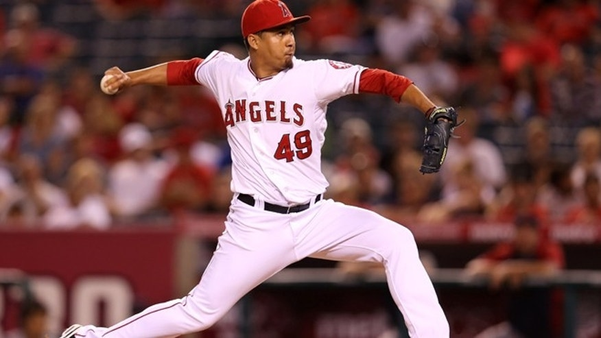 ANAHEIM, CA - AUGUST 14:  Closer Ernesto Frieri #49 of the Los Angeles Angels of Anaheim pitches in the ninth inning on his way to picking up a save against the Cleveland Indians at Angel Stadium of Anaheim on August 14, 2012 in Anaheim, California. The Angels won 9-6.  (Photo by Stephen Dunn/Getty Images)