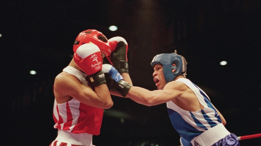 Orlando Cruz Torres of Puerto Rico (blue) lands a left at the Sydney Exhibition Centre during the Sydney Olympic Games.
