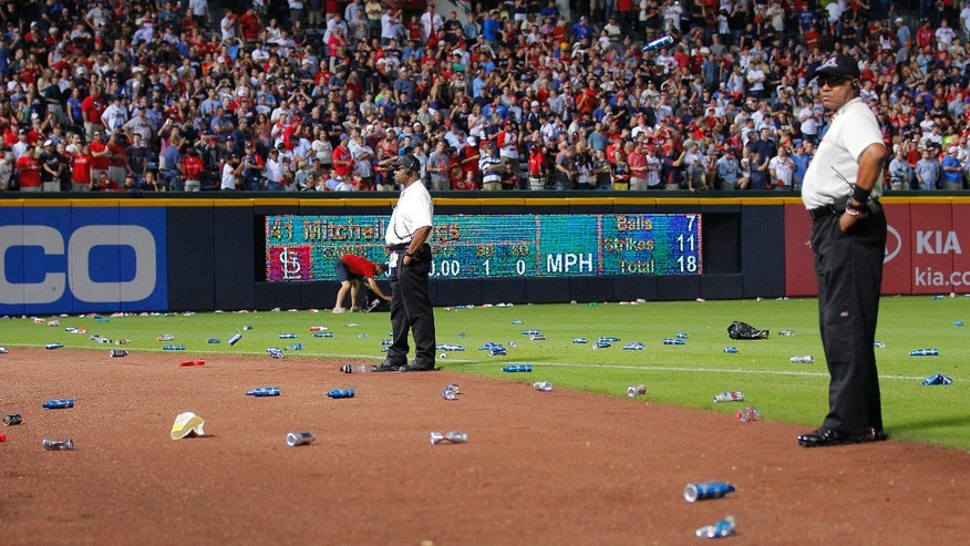 Oct. 5, 2012: Atlanta Braves officials pick up trash on the field as security stand by during the eighth inning of the National League wild card playoff baseball game against the St. Louis Cardinals.