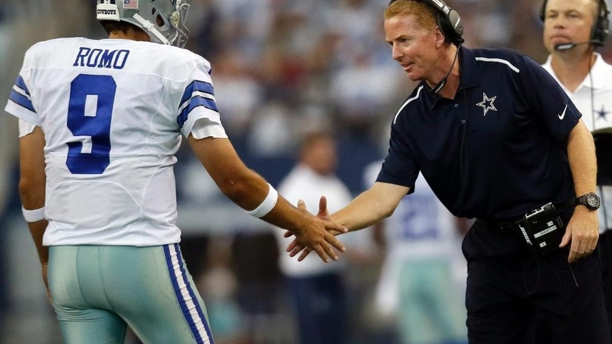 Dallas Cowboys' Tony Romo (9) shakes hands with head coach Jason Garrett after a touchdown against the San Francisco 49ers during the second half of an NFL football game, Sunday, Sept. 7, 2014, in Arlington, Texas. (AP Photo/Tony Gutierrez)