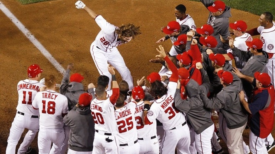 Washington Nationals' Jayson Werth leaps onto home plate after hitting a walk-off home run in the ninth inning against the St. Louis Cardinals in Game 4 of the National League baseball division series, Thursday, Oct. 11, 2012, in Washington.