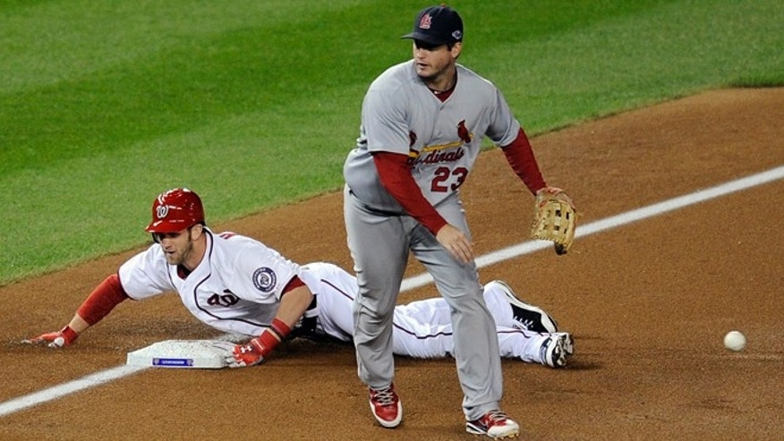 Oct. 12, 2012: Washington Nationals' Bryce Harper, back, slides into third base for a triple as the throw goes wide of St. Louis Cardinals third baseman David Freese in the first inning of Game 5 of the National League division baseball series in Washington.