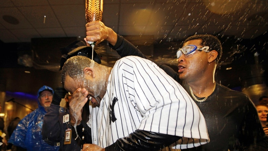 Oct. 12, 2012: New York Yankees starting pitcher CC Sabathia is doused with champagne by teammate Ivan Nova, right, after Game 5 of the American League division baseball series against the Baltimore Orioles in New York.