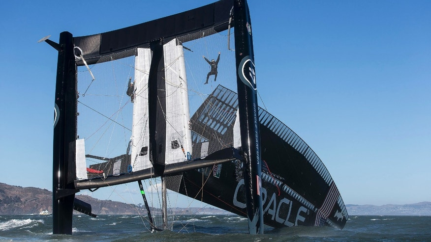 Oct. 16, 2012: Photo provided by Oracle Team USA, crew members hang from the mesh netting after the Oracle Team USA AC72 boat capsized on San Francisco Bay in San Francisco.