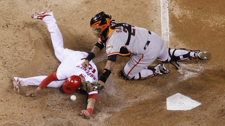 San Francisco catcher Hector Sanchez (right) is unable to handle the throw as Cardinals' Matt Carpenter slides towards home on a single by Matt Holliday in fifth inning action during Game 4 of the National League Championship Series.