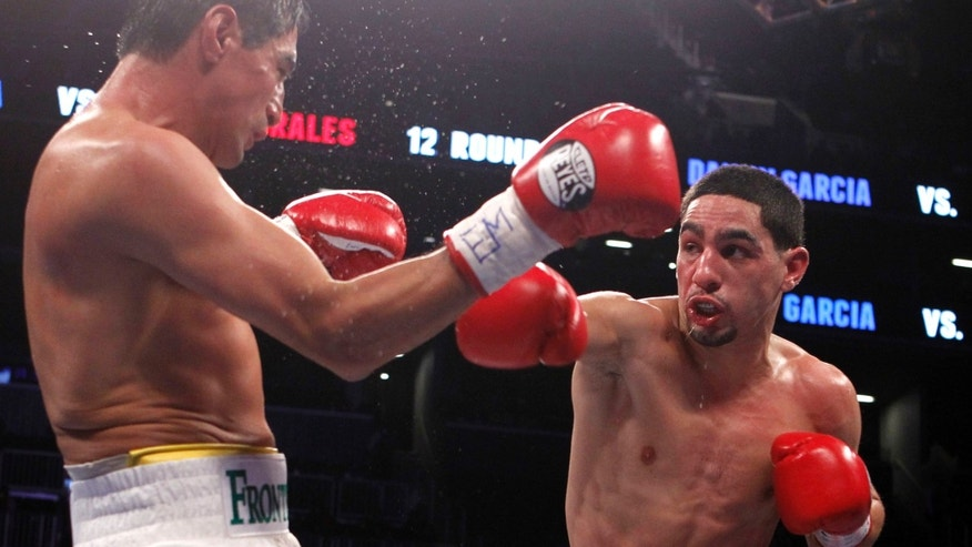 Danny Garcia, right, punches Mexico's Erik Morales during their WBC and WBA super lightweight title bout at the Barclays Center, Saturday, Oct. 20, 2012, in New York.  Garcia knocked out Morales in the fourth round. (AP Photo/Jason DeCrow)