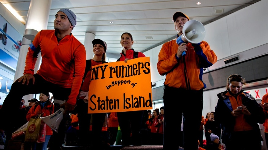 Dr. Jordan Metzl, right, addresses a crowd of runners who would have run the New York Marathon Sunday, Nov. 4, 2012, at the Staten Island ferry terminal in New York. With the cancellation of the New York Marathon, hundreds of  runners, wearing their marathon shirts and backpacks full of supplies, took the ferry to hard-hit Staten Island and ran to hard-hit neighborhoods to help. (AP Photo/Craig Ruttle)