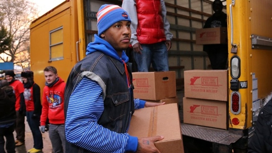 NEW YORK, NY - NOVEMBER 08:  Carmelo Anthony helps distribute aid as part of his foundation's Storm Relief Project with Feed the Children and Metro Ministries in the Red Hook neighborhood of Brooklyn on November 8, 2012 in New York City.  (Photo by Neilson Barnard/Getty Images)