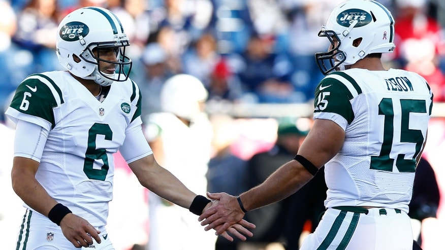 Mark Sanchez #6 and Tim Tebow #15 of the New York Jets high five each other during warm ups prior to the game against the New England Patriots on October 21, 2012.  (Photo by Jared Wickerham/Getty Images)