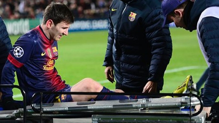 Lionel Messi is carted off the field after injuring his left knee on December 5, 2012, Barcelona. (AP Photo/Manu Fernandez)