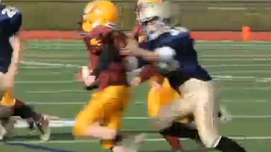 This undated screen shot shows Caroline Pla, right, making a tackle during a football game.