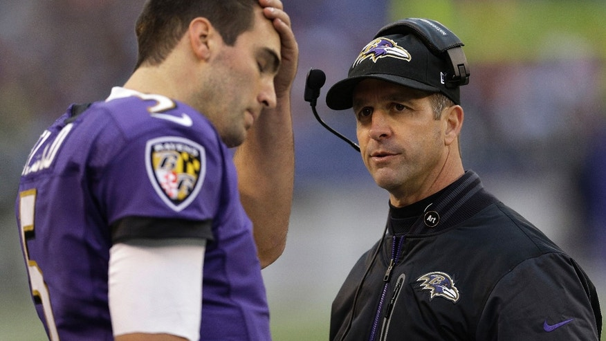 Baltimore Ravens head coach John Harbaugh looks at quarterback Joe Flacco as he walks off the field during the second half of an NFL football game against the Denver Broncos in Baltimore, Sunday, Dec. 16, 2012. (AP Photo/Patrick Semansky)