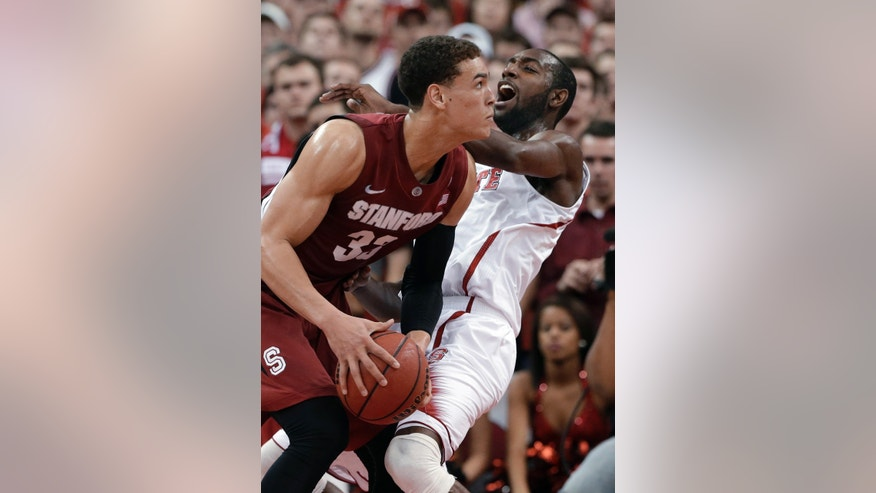 North Carolina State's C.J. Leslie, right, defends on a drive by Stanford's Dwight Powell (33) during the first half of an NCAA college basketball game in Raleigh, N.C., Tuesday, Dec. 18, 2012. (AP Photo/Gerry Broome)