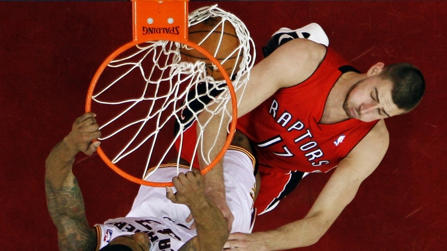Cleveland Cavaliers' Alonzo Gee, left, dunks on Toronto Raptors' Jonas Valanciunas (17), of Lithuania, in the first half of an NBA basketball game, Tuesday, Dec. 18, 2012, in Cleveland. (AP Photo/Mark Duncan)
