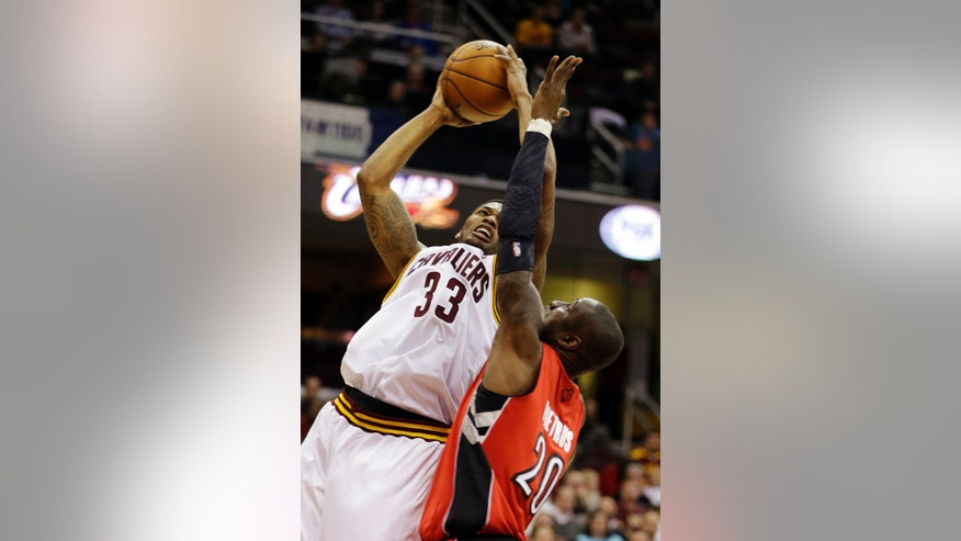 Cleveland Cavaliers' Alonzo Gee (33) shoots over Toronto Raptors' Mickael Pietrus (20), of France, in the second quarter of an NBA basketball game, Tuesday, Dec. 18, 2012, in Cleveland. (AP Photo/Mark Duncan)