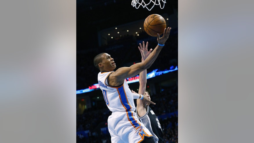 Oklahoma City Thunder guard Russell Westbrook (0) shoots in front of San Antonio Spurs guard Nando De Colo (25) in the second quarter of an NBA basketball game in Oklahoma City, Monday, Dec. 17, 2012. (AP Photo/Sue Ogrocki)