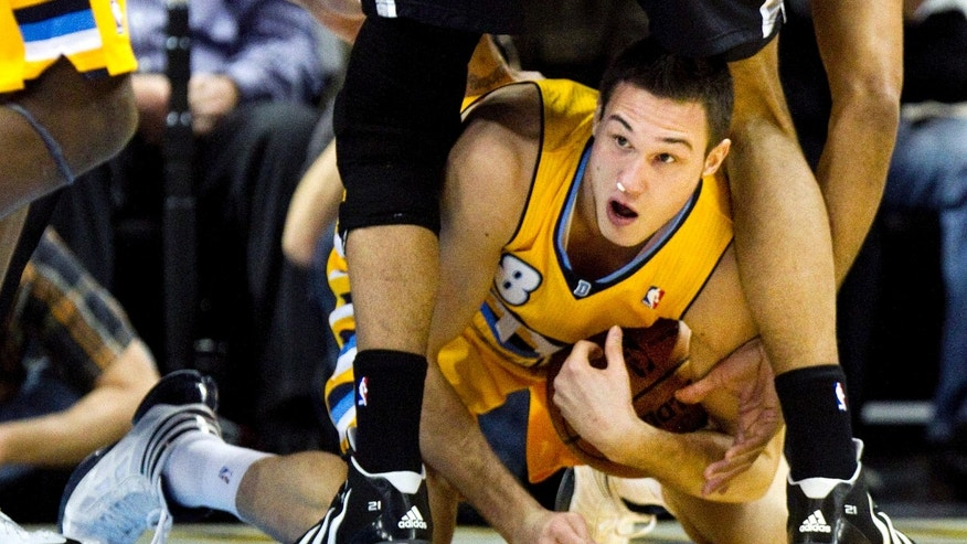 Denver Nuggets' Danilo Gallinari (8) grabs a loose ball while crawling between the legs of San Antonio Spurs' Tim Duncan during the first quarter of an NBA basketball game Tuesday, Dec. 18, 2012 in Denver. (AP Photo/Barry Gutierrez)