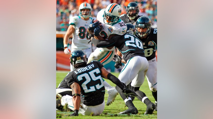 Miami Dolphin's Reggie Bush (22) is tackled by Jacksonville Jaguars' Mike Harris (20) as Dwight Lowery (25) and Jason Babin (58) watch during an NFL football game, Sunday, Dec. 16, 2012, in Miami. The Dolphins won 24-3. (AP Photo/The Miami Herald, Al Diaz)  MAGS OUT