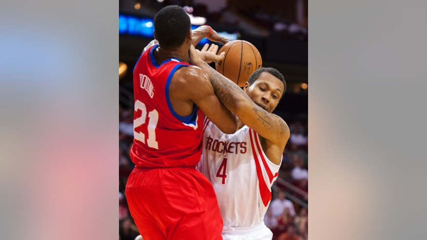 Houston Rockets' Greg Smith (4) is fouled by Philadelphia 76ers' Thaddeus Young (21) during the first quarter of an NBA basketball game, Wednesday, Dec. 19, 2012, in Houston. (AP Photo/Dave Einsel)