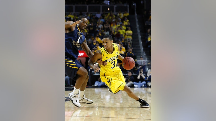 Michigan guard Trey Burke (3) rushes through the defense of West Virginia forward Dominique Rutledge (1) in the second half of their NCAA college basketball game at the Barclays Center, Saturday, Dec. 15, 2012, in New York. Michigan left the court victorious with a 81-66 win over West Virginia. (AP Photo/John Minchillo)