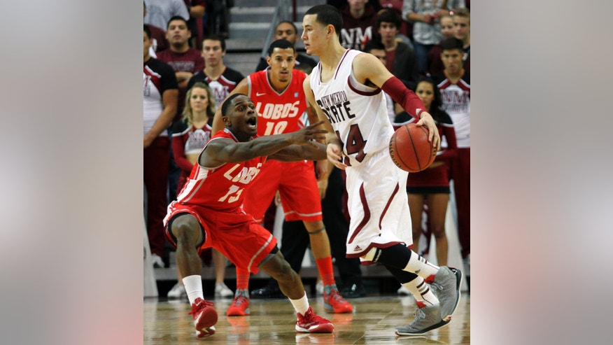 New Mexico's Jamal Fenton, left, reaches to steal the ball from New Mexico State's Terrel de Rouen during the first half of an NCAA college basketball game in Las Cruces, N.M., Wednesday, Dec. 19, 2012. New Mexico's Kendall Williams watches at rear. (AP Photo/Victor Calzada)
