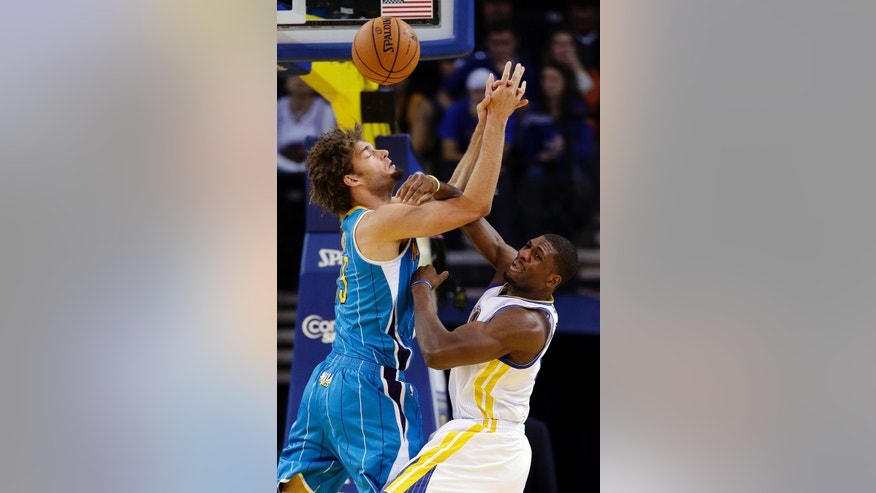 New Orleans Hornets' Robin Lopez, left, battle for a rebound against Golden State Warriors' Festus Ezeli during the first half of an NBA basketball game in Oakland, Calif., Tuesday, Dec. 18, 2012. (AP Photo/Marcio Jose Sanchez)