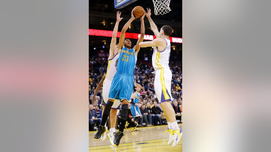 New Orleans Hornets' Anthony Davis (23) shoots between Golden State Warriors' David Lee, left, and Klay Thompson during the first half of an NBA basketball game in Oakland, Calif., Tuesday, Dec. 18, 2012. (AP Photo/Marcio Jose Sanchez)