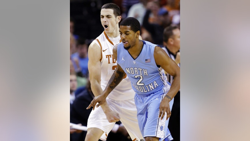 Texas' Ioannis Papapetrou, left, reacts next to North Carolina's Leslie McDonald (2) after scoring during the first half of an NCAA college basketball game, Wednesday, Dec. 19, 2012, in Austin, Texas. (AP Photo/Eric Gay)