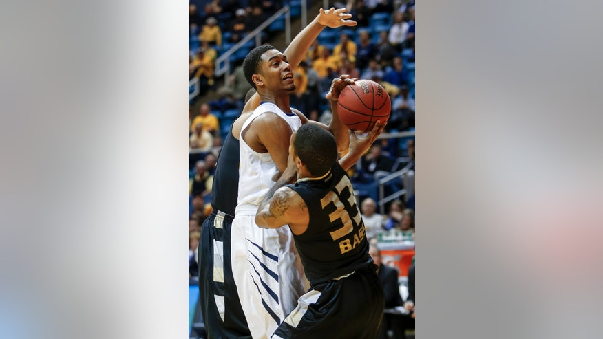 West Virginia's Terry Henderson, center, is fouled by Oakland's Ryan Bass (33) during the first half of an NCAA college basketball game, Wednesday, Dec. 19, 2012, in Morgantown, W.Va. (AP Photo/David Smith)
