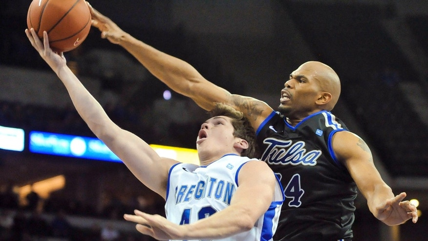 Tulsa's Scottie Haralson (44) tries to block a shot by Creighton's Alex Olsen (40) during their Wednesday, Dec. 19, 2012, NCAA college  basketball game in Omaha, Neb. (AP Photo/Dave Weaver)