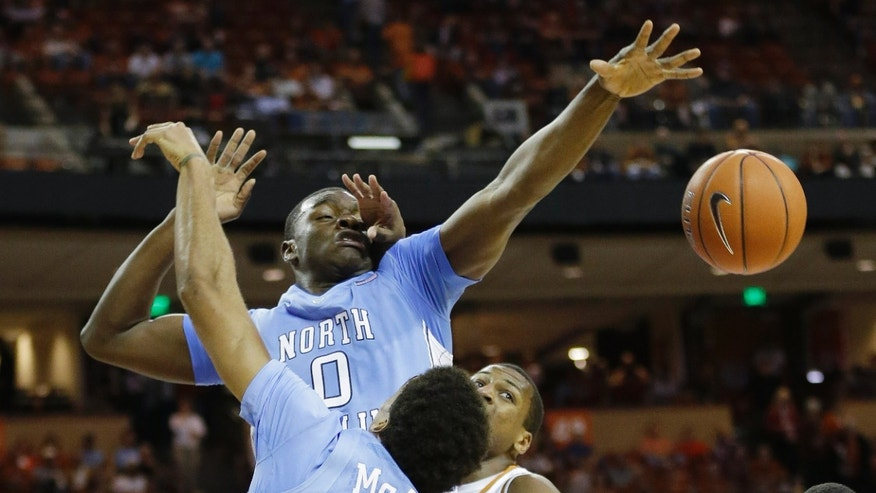 North Carolina's Joel James (0) is fouled by Texas' Jonathan Holmes, right, during the first half of an NCAA college basketball game on Wednesday, Dec. 19, 2012, in Austin, Texas. (AP Photo/Eric Gay)