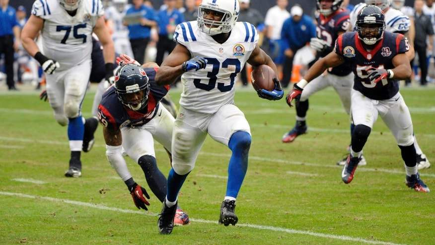 Indianapolis Colts running back Vick Ballard (33) rushes for a gain as Houston Texans' Glover Quin (29) and Darryl Sharpton (51) pursue in the third quarter of an NFL football game on Sunday, Dec. 16, 2012, in Houston. (AP Photo/Dave Einsel)