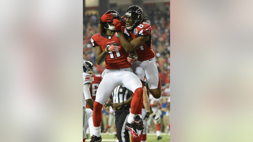 Atlanta Falcons wide receivers Julio Jones (11) and Roddy White (84) celebrate a Jones touchdown during the second half of an NFL football game against the New york Giants, Sunday, Dec. 16, 2012, in Atlanta. (AP Photo/Rich Addicks)