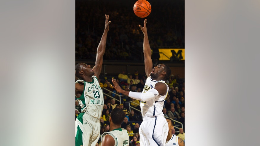 Eastern Michigan forward Glenn Bryant (23) defends a shot-attempt by Michigan guard Tim Hardaway Jr., right, in the first half of an NCAA college basketball game on Thursday, Dec. 20, 2012, at Crisler Center in Ann Arbor, Mich. (AP Photo/Tony Ding)