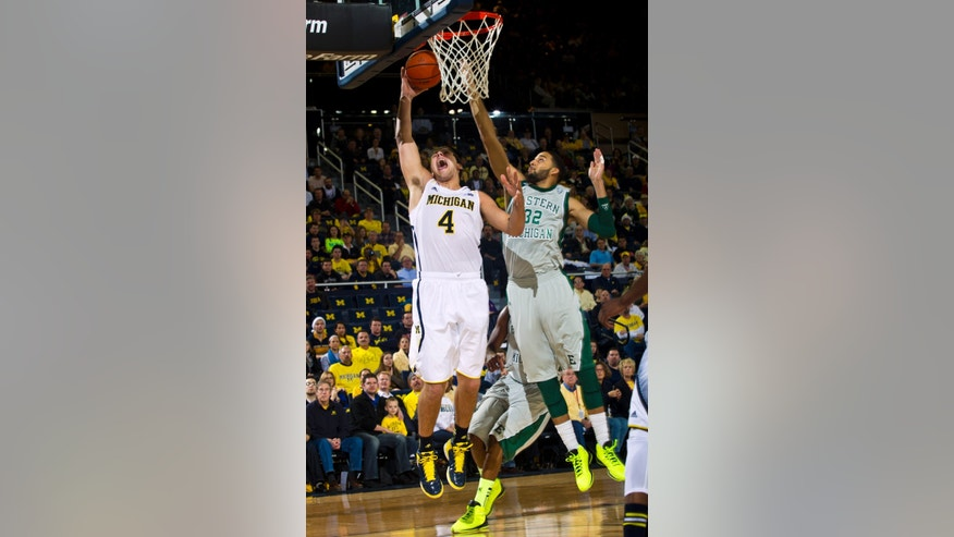 Michigan forward Mitch McGary (4) goes to the basket while defended by Eastern Michigan forward Jamell Harris (32) in the first half of an NCAA college basketball game on Thursday, Dec. 20, 2012, at Crisler Center in Ann Arbor, Mich. (AP Photo/Tony Ding)