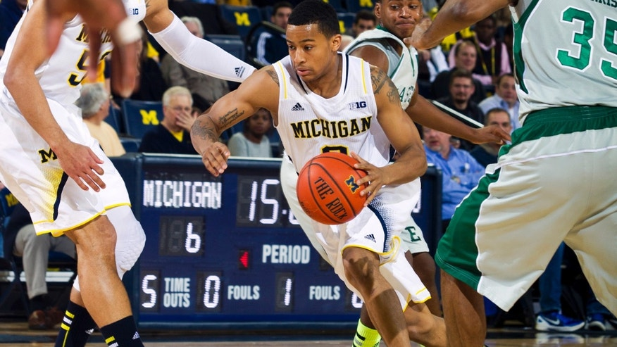 Michigan guard Trey Burke, center, drives against Eastern Michigan in the first half of an NCAA college basketball game, Thursday, Dec. 20, 2012, at Crisler Center in Ann Arbor, Mich. (AP Photo/Tony Ding)