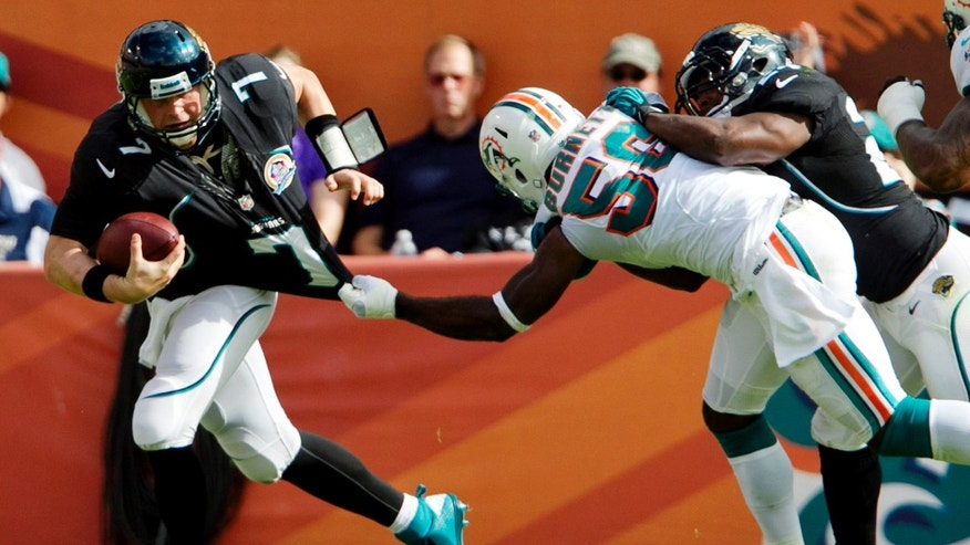 Miami Dolphins linebacker Kevin Burnett, second from right, tackles Jacksonville Jaguars quarterback Chad Henne (7) by his jersey during the first quarter of an NFL football game, Sunday, Dec. 16, 2012, in Miami. The Dolphins won 24-3. (AP Photo/The Miami Herald, Joe Rimkus Jr.)  MAGS OUT