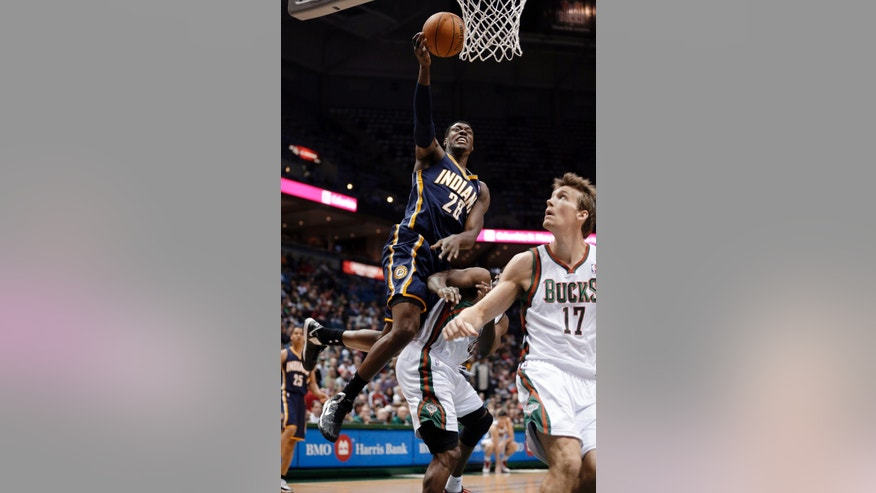 Indiana Pacers' Ian Mahinmi (28) is fouled as he goes up for a shot against Milwaukee Bucks' Mike Dunleavy (17) and Ekpe Udoh during the second half of an NBA basketball game Tuesday, Dec. 18, 2012, in Milwaukee. The Bucks won 98-93. (AP Photo/Morry Gash)