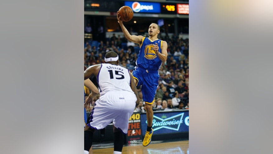 Golden State Warriors guard Stephen Curry, right, drives to the basket against Sacramento Kings defender DeMarcus Cousins during the first half of an NBA basketball game in Sacramento, Calif., Wednesday, Dec. 19, 2012. (AP Photo/Steve Yeater)