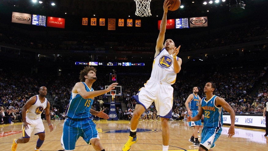 Golden State Warriors' Stephen Curry (30) scores past New Orleans Hornets' Robin Lopez (15) and Brian Roberts (22) during the second half of an NBA basketball game in Oakland, Calif., Tuesday, Dec. 18, 2012. Golden State won 103-96. (AP Photo/Marcio Jose Sanchez)
