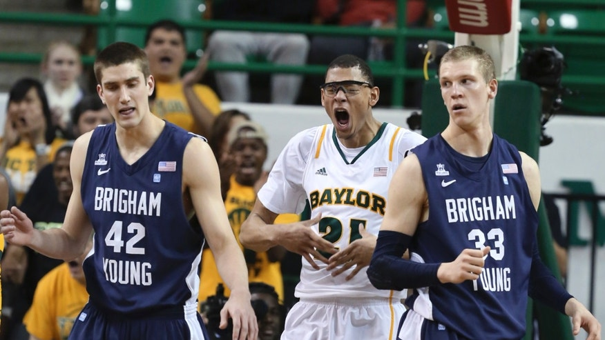 Baylor's Isaiah Austin, center, lets out a yell between Brigham Youngs' Ian Howard, left, and Nate Austin (33) after being fouled in the first half of an NCAA college basketball game, Friday, Dec. 21, 2012,  in Waco, Texas. (AP Photo/Waco Tribune Herald, Rod Aydelotte)
